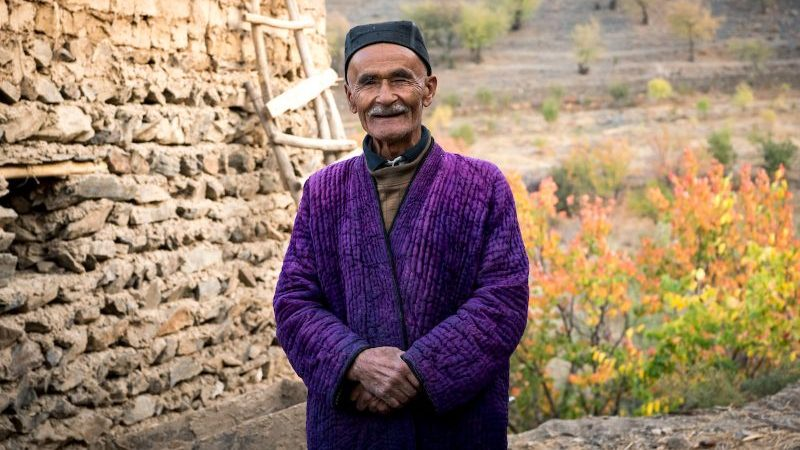 Local Uzbek man in traditional purple dress stands outside his house and poses for a photo