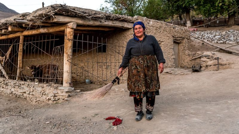Uzbek woman stands in front of her village home with a broom.