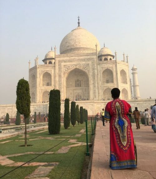 A woman standing in front of the Taj Mahal