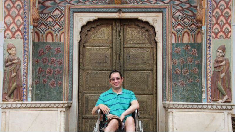 A man in a wheelchair sits in front of an ornate door at a palace