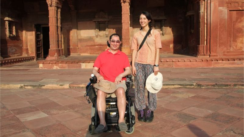 A man sits in a wheelchair next to a young woman in India.