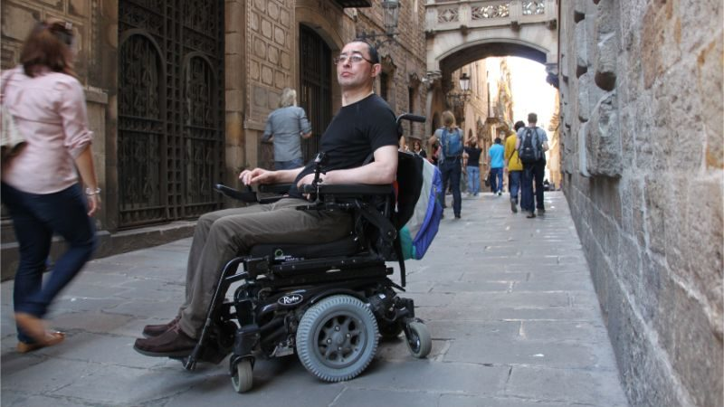 A man in a wheelchair in a cobbled lane in Spain