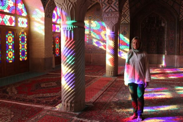 A woman standing inside a colourful mosque in Iran