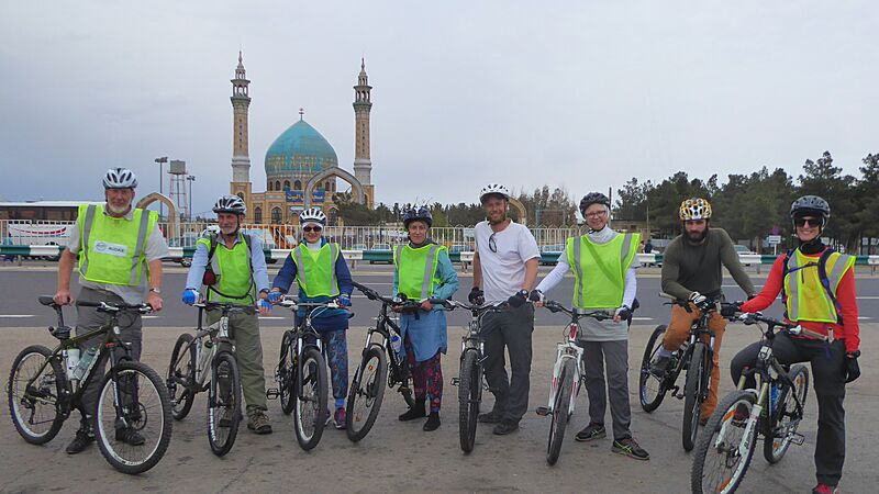 A group of cyclists in front of a mosque in Iran