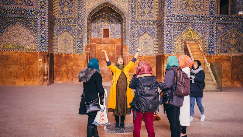 A group of travellers in a mosque in Iran.