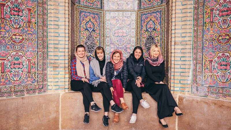 A group of smiling travellers in Iran at a mosque