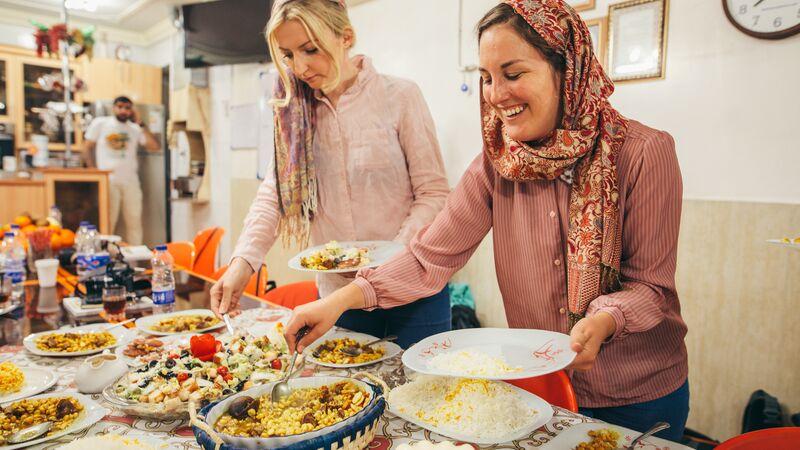 Two women serving food in Iran
