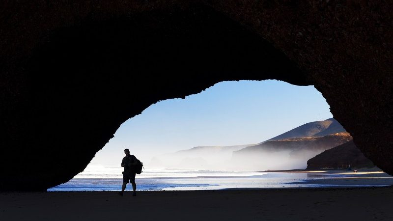 Person standing under a stone archway.