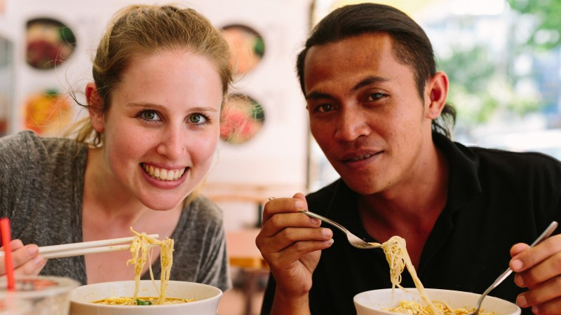 A solo traveller eating laksa in Malaysia