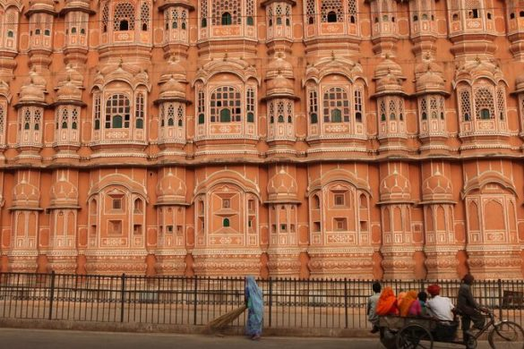 Woman sweeping the road in front of a pink building in India