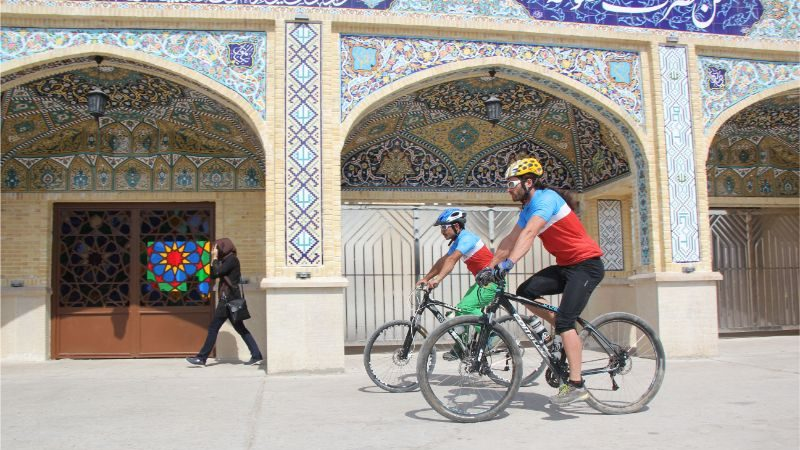 Two cyclists riding bikes past a mosque in Iran