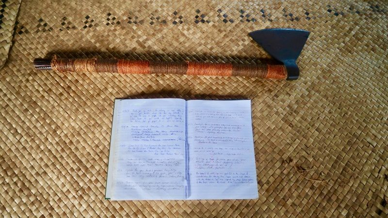 An axe and a guestbook on a table