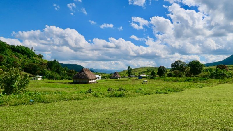 A rural village, green grass and blue sky in Fiji