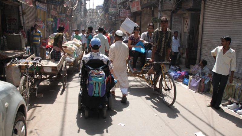 A man in a wheelchair navigating traffic in India
