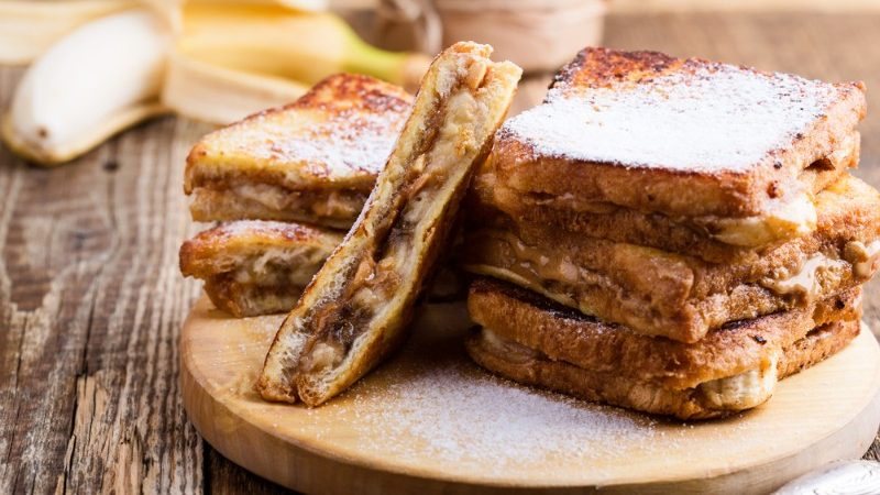 Grilled banana sandwiches on a wooden plate
