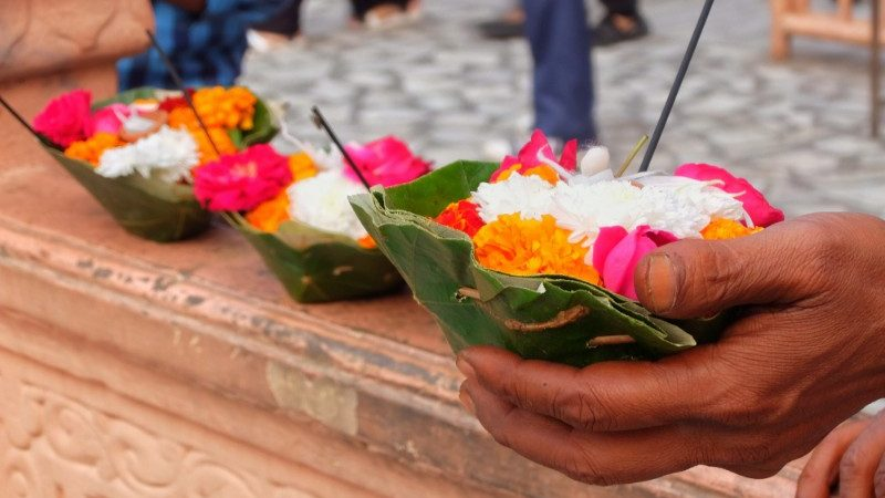 Image of a hand holding flowers to use in the ceremony.