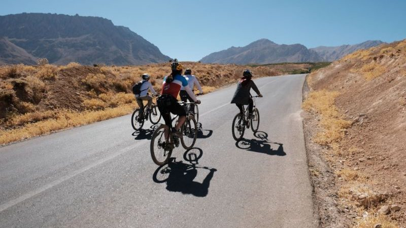 A group of cyclists ride down a quiet road in Iran