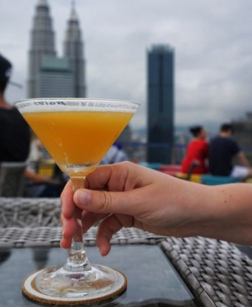 Cocktail on a rooftop with tall building in the background