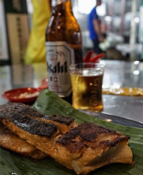 Grilled fish on a banana leaf and a beer in the background