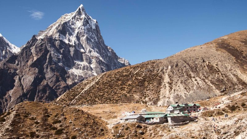 Small gueshouse set against the rocky peaks of the Himalayas