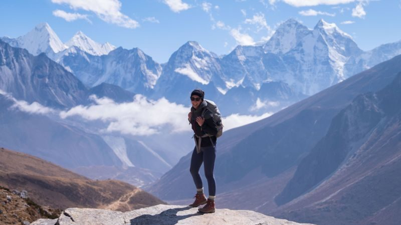 Person standing with the peaks of the Himalayas in the background wearing a backpack and similing