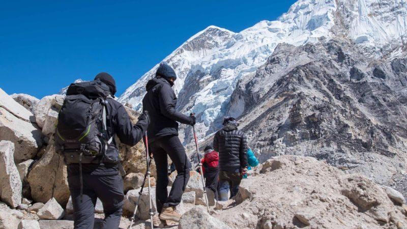 Group of people hiking up to Everest Base Camp with snow capped mountains in the background.
