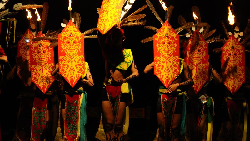 a group of Dayak dancers perform traditional warrior dance