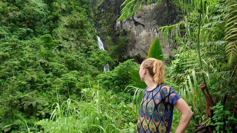 A girl standing in front of a waterfall in Fiji