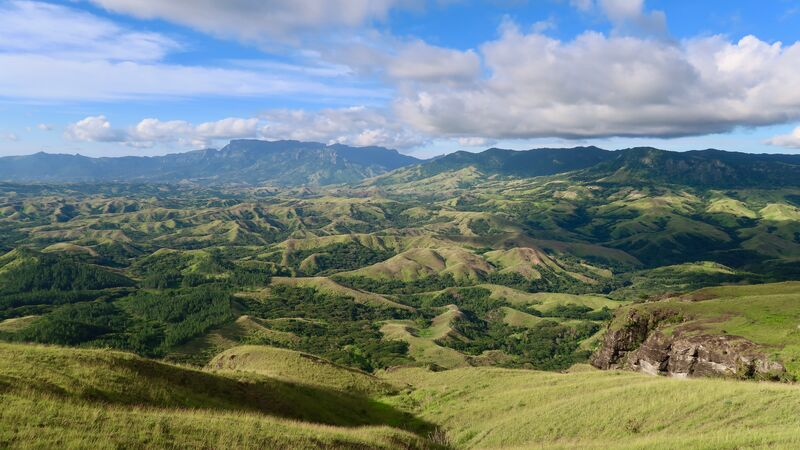 Rolling green hills and blue sky on a Fiji island