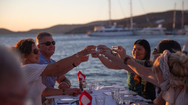 A group of travellers cheers their drinks at sunset.