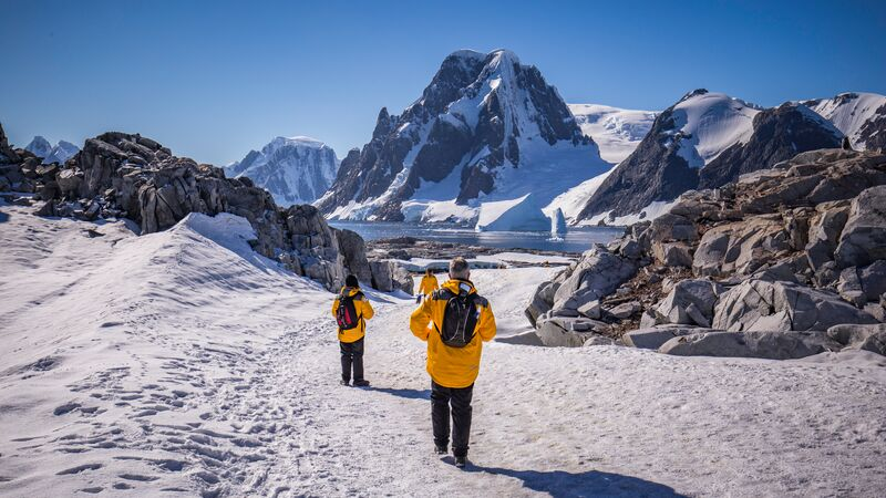 Three travellers exploring Antarctica