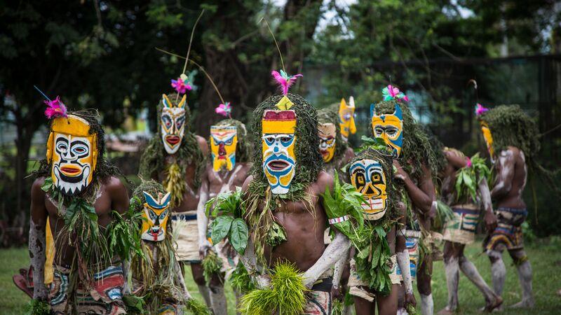 dancers wearing colourful masks in Papua New Guinea