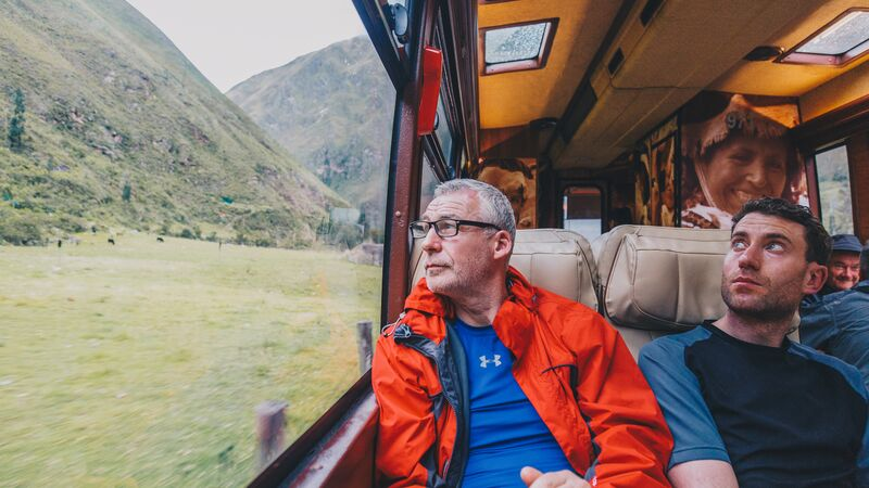 A man looks out the window on a train to Machu Picchu