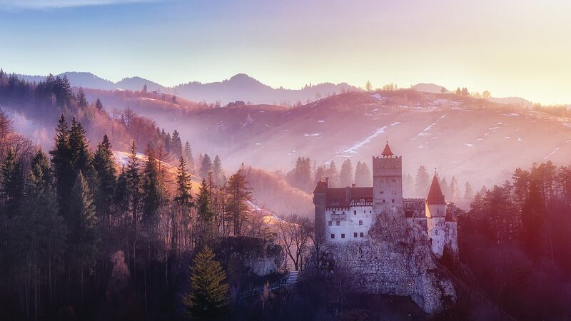 Bran or Dracula Castle in Transylvania, Romania. The castle is located on top of a mountain, sunset light