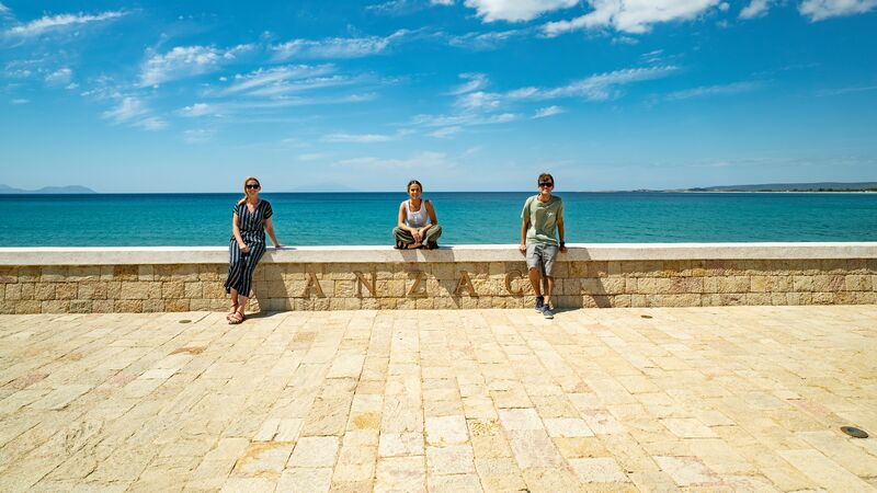 Three travellers sitting on a wall overlooking the sea in Turkey