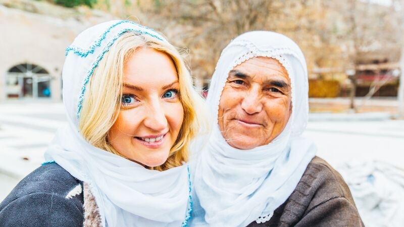 A traveller smiles with a local woman in Turkey