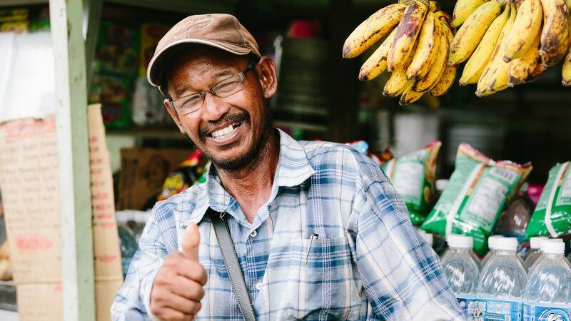 Smiling man selling bananas giving a thumbs up
