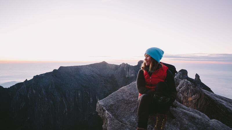 A woman wearing a blue beanie on the top of a mountain