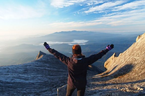 A woman stands with her arms in the air on the top of Mt Kinabalu