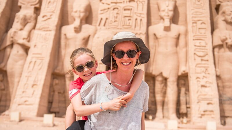 A mother gives her daughter a piggyback in Egypt