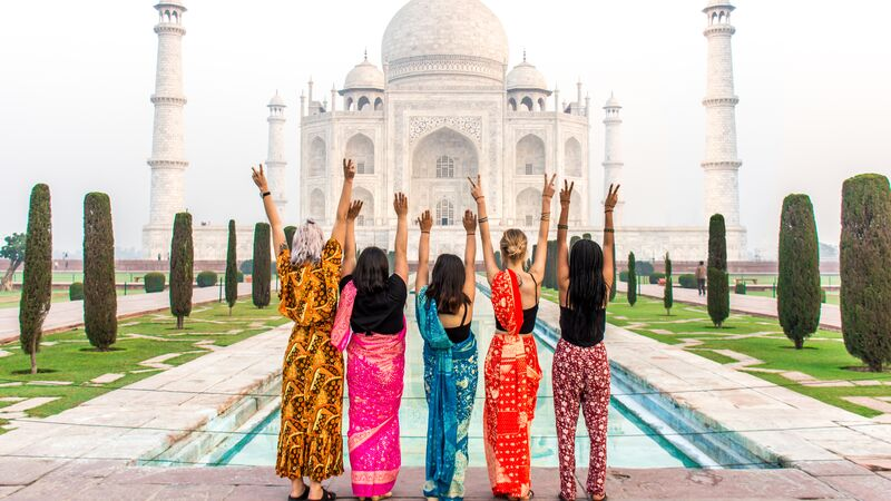 Five woman facing the Taj Mahal with their arms up