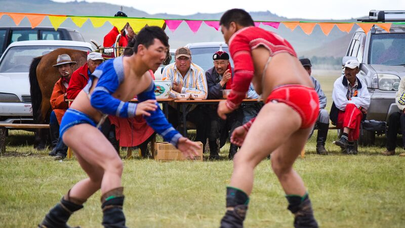 Two people wrestling in Mongolia at Naadam Festival