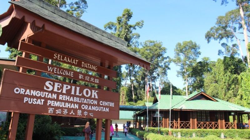 A sign for Sepilok with a house in the background
