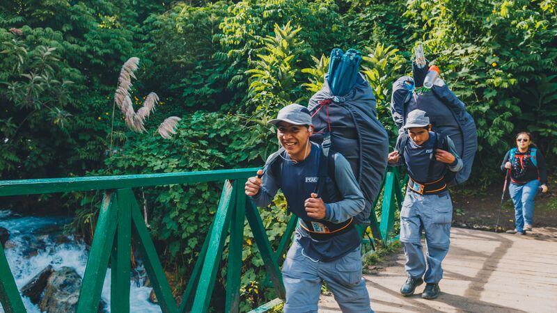 Two porters crossing a bridge, giving the camera a thumbs up