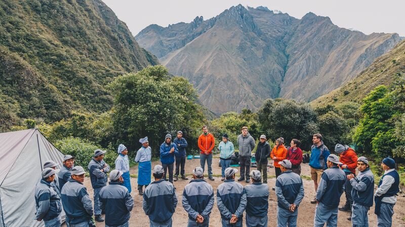 A group of porters, travellers and guides stand in a circle on the Inca Trail
