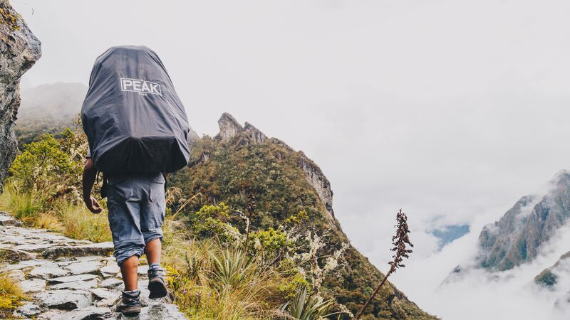 A porter with a big bag on his back on the Inca Trail