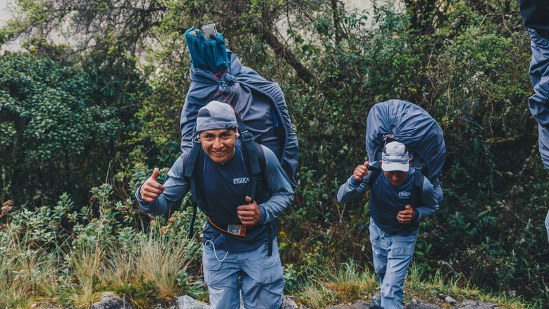 Two porters wearing backpacks giving the thumbs up