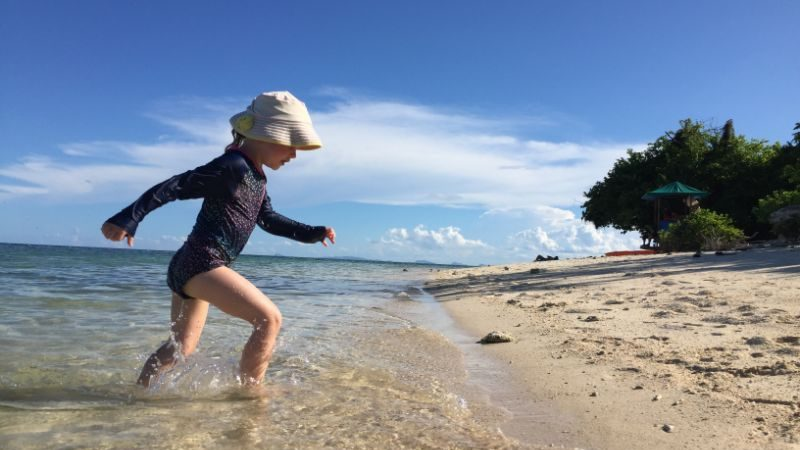 A little girl in a hat playing at the beach