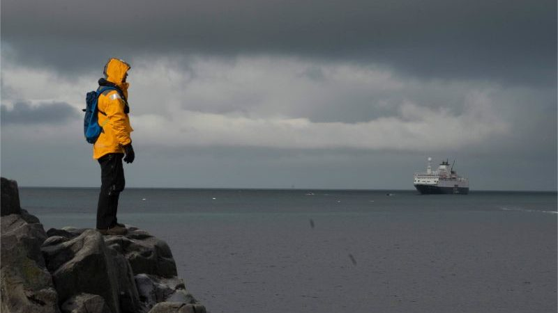 A person wearing a yellow jacket standing on a rock looking at a ship