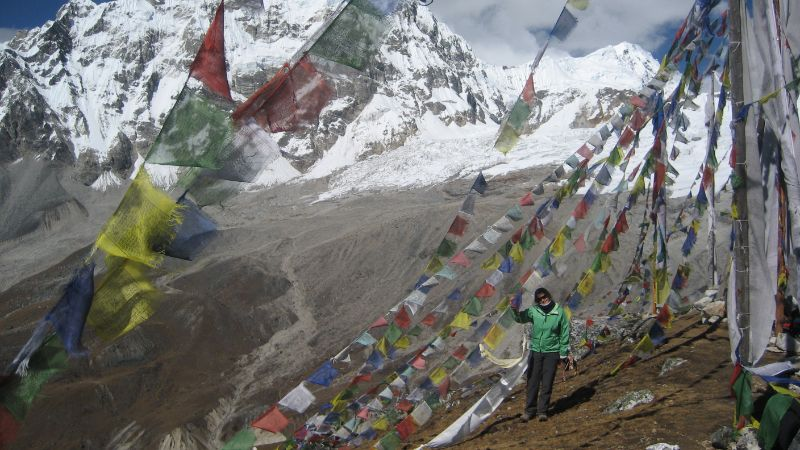A female hiker stands under strings of flags in Nepal